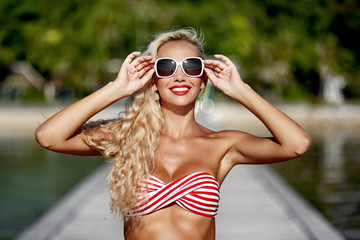 Fashion portrait of beautiful cute blonde woman wearing sunglass