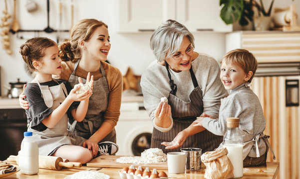 happy family a grandmother with her daughter and grandchildren cooks in kitchen, kneads dough, bakes cookies.