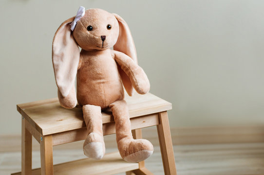 Kids soft toy rabbit with bow sitting on wooden chair