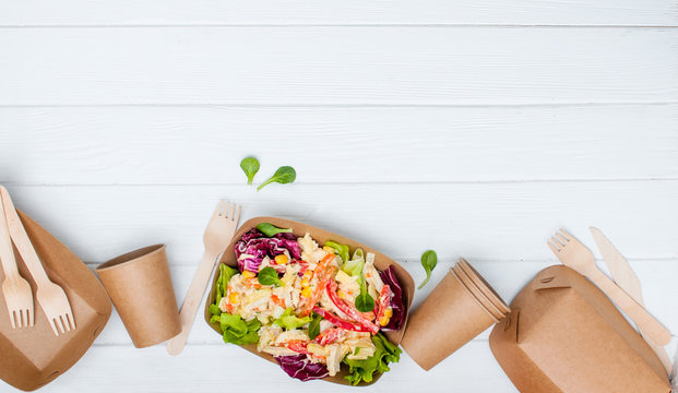 Vegetable salad in the kraft paper food containers on white background with copy space
