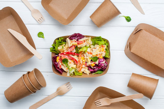 Vegetable salad in the brown kraft containers on wooden background