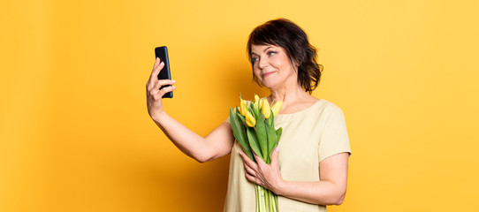 Beautiful old woman with professional smokey make-up and hairstyle holding tulip flowers on the pink background. Taking video call by the smartphone .Concept spring