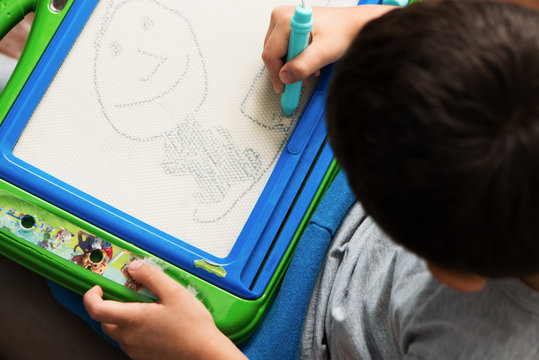 child drawing on a board top view