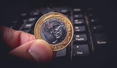 Moeda de 1 Real, Moeda brasileira. Foto ilustrativa tendo como cenário o teclado de um Pc Desktop sobre as compras na internet.