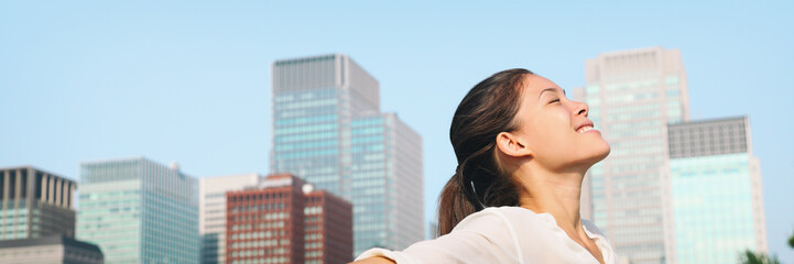 Happy healthy woman taking deep breath in city clean air for pollution concept panoramic lansdcape header banner. Asian lady in Asia face portrait with closed eyes.