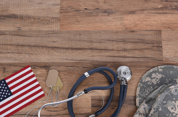 Military and Veterans Health Care Concept. Dog tags, American Flag, military camo hat and stethoscope on a wood background.