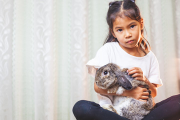 Cute asian child girl carrying and playing with cute Holland lop rabbit with love and tenderness at easter festive