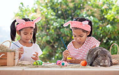 Two cute asian child girls drawing and painting on easter eggs together prepare for easter day. Children and Holland lop rabbit in easter festive.