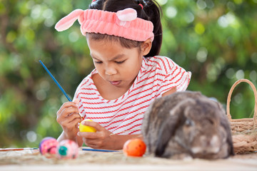 Cute asian child girl drawing and painting on easter eggs prepare for easter day. Child and Holland lop rabbit in easter festive.