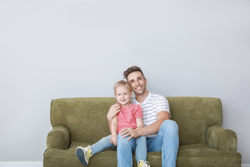Happy young father and daughter sitting on sofa near light wall