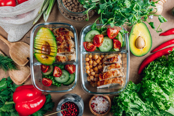 Zelfklevend Fotobehang Kruidenierswinkel Healthy meal prep containers with chickpeas, chicken, tomatoes, cucumbers and avocados. Healthy lunch in glass containers on beige rustic background. Zero waste concept. Selective focus.