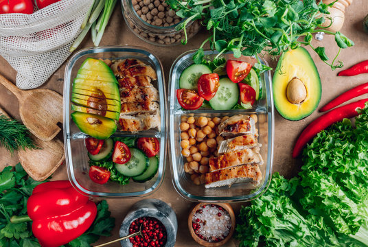 Healthy meal prep containers with chickpeas, chicken, tomatoes, cucumbers and avocados. Healthy lunch in glass containers on beige rustic background. Zero waste concept. Selective focus.