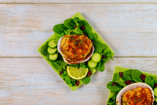 Stuffed clams with crabmeat and bread crumbs with salad and lemon. Seafood concept.
