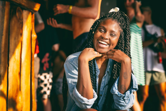 Charming beautiful young african american girl woman with black pigtails with piercings on her face sitting at a bar during a party