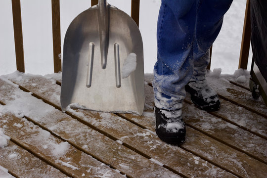 Close up view of an unseen person shoveling deep snow of a wooden deck surface