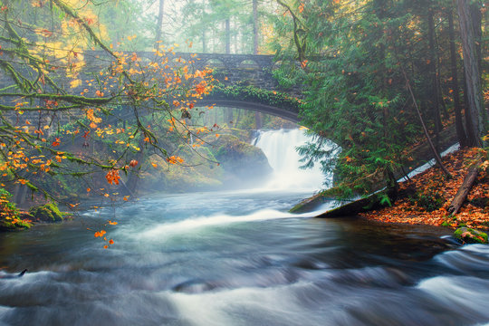 A fall mist envelopes a bridge and water fall