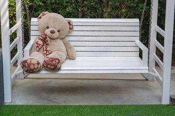 Cute teddy bear sitting on a white wooden swing in the garden and green natural background decoration