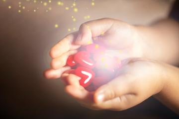 光を放つ沢山の赤いハートのモチーフを持つ子供の手
