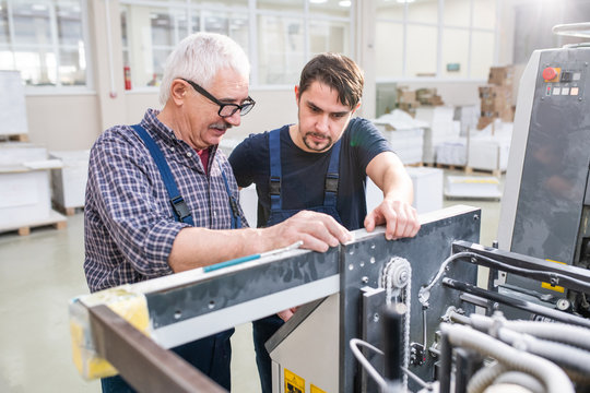 Senior worker in glasses explaining printing machine setups to young colleague at modern factory
