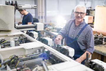Portrait of smiling senior repair specialist in glasses adjusting printing machine at factory