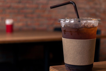 Close up of take away plastic cup of iced black coffee