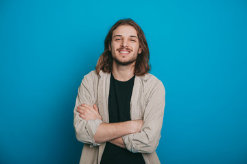 The picture of a glad man with crossed arms , beard and long hair ,dressed in a shirt posing on a blue background