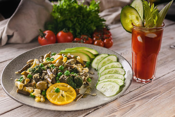 Vegetarian organic food. Beans and green peas salad, vegetables and herbs, tomato juice on a wooden background. Veggie nutrition