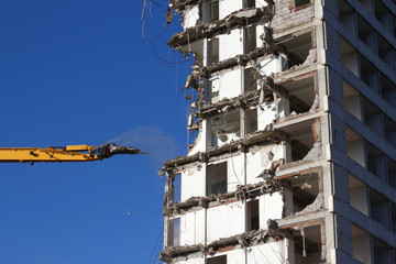 A tower block is carefully being demolished by a yellow excavator with water sprayers