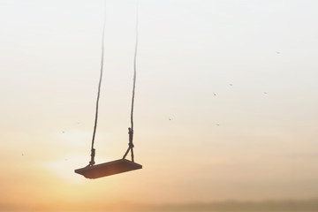 lonely swing surreally hanging from the sky
