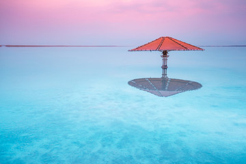 Dead Sea beach. Sun umbrella in water. Minimalist landscape Wall mural
