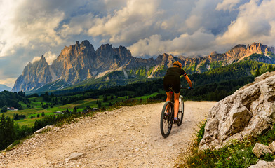 Tourist cycling in Cortina d'Ampezzo, stunning rocky mountains on the background. Woman riding MTB...