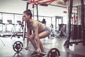 sporty woman does the exercises with bar. photo of muscular woman in sportswear. fitness women exercising are lifting bar at vintage fitness gym. concept strength and motivation.