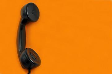 Vieux combiné téléphonique sur fond orange