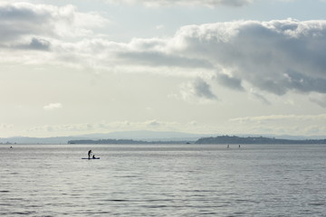 Paddle boarding in distance on surface of large very calm harbor in back light.