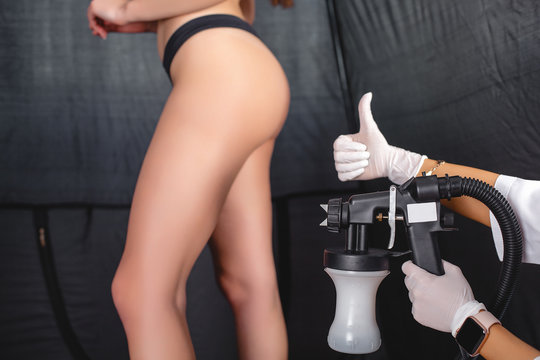Beauty master applying fake tan on woman`s body. Ekotanning. Ecological tan. Female making tanning in tan studio. Client making an express bronzing by airbrush-pistol.