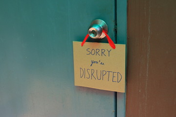 Closeup handwriting cardboard sign with message read sorry you are disrupted hanging on doorknob of wooden door, disruption concept