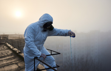 Scientist wearing protective outfit and gas mask, working on roof of high building, conducting the study, using blue reagent in glass flask over sunrise