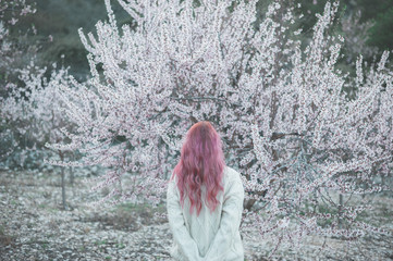 Pink haired woman in front of blossom almond tree