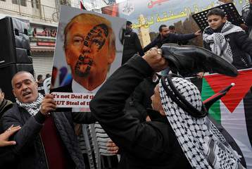 Palestinian demonstrator hits with a shoe a poster depicting U.S. President Trump during a rally in support of Palestinian President Abbas and against Trump's Middle East peace plan, in Ramallah in the Israeli-occupied West Bank