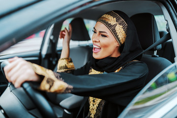 Cheerful gorgeous positive muslim woman in traditional wear driving her new car, listening music and singing.