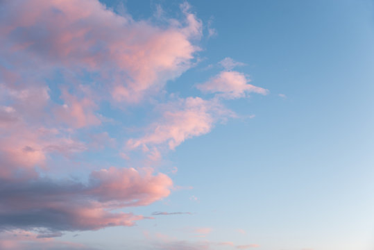 dreamy sky background, one half with fluffy pink clouds and blue side with copy space