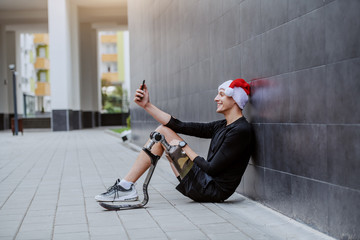 Fotomurales - Cheerful Caucasian sportsman with artificial leg and with santa hat on head sitting on ground, leaning on wall and taking selfie.