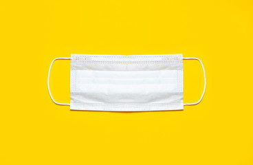 Medical mask on yellow background flat lay top view with copy space. Protection against virus,...