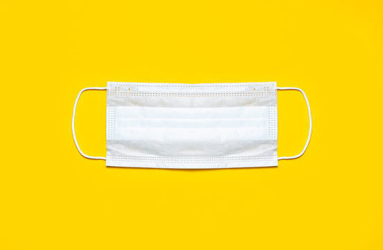Medical mask on yellow background flat lay top view with copy space. Protection against virus, coronavirus, flu, colds, diseases. Traditional medical tool, concept of health. Medical background