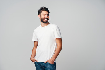Handsome young man smiling isolated on grey background wearing casual t-shirt and jeans looking away Wall mural
