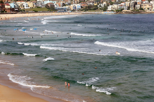 A group of people are swimming in the ocean at the Bondy beach in Australia on sunny day