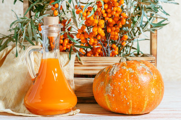 Vegetarian food healthy nutrition preserving harvest of ripe juicy sea buckthorn and homemade pumpkin, preparing fresh healthy vitamin drink and healing broth. Bottle juice branches orange berry fruit