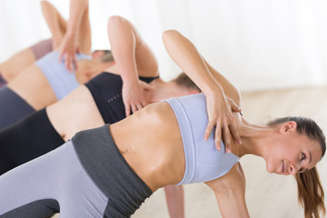 Fotomurales - Group of young sporty attractive women in yoga studio, practicing yoga lesson with instructor, forming a line in Trikanasana asana pose. Healthy active lifestyle, working out indoors in gym.