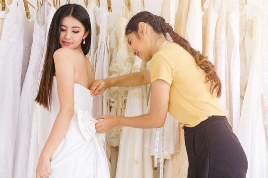Asian female stylist helping the bride zipping up the wedding dress.