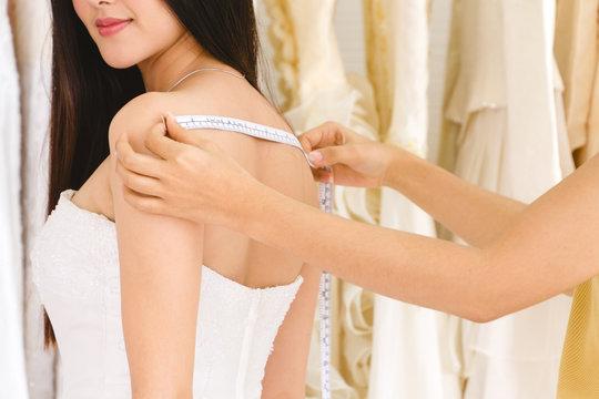 Female dressmaker measuring woman's back for wedding dress.